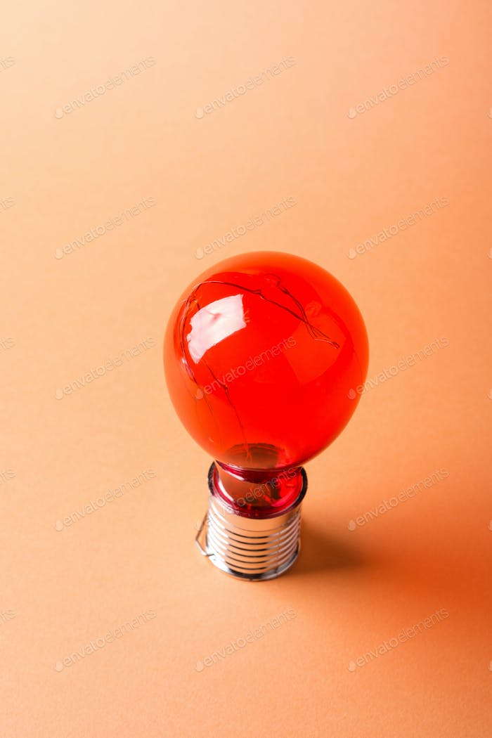 Red solar light bulb on orange
