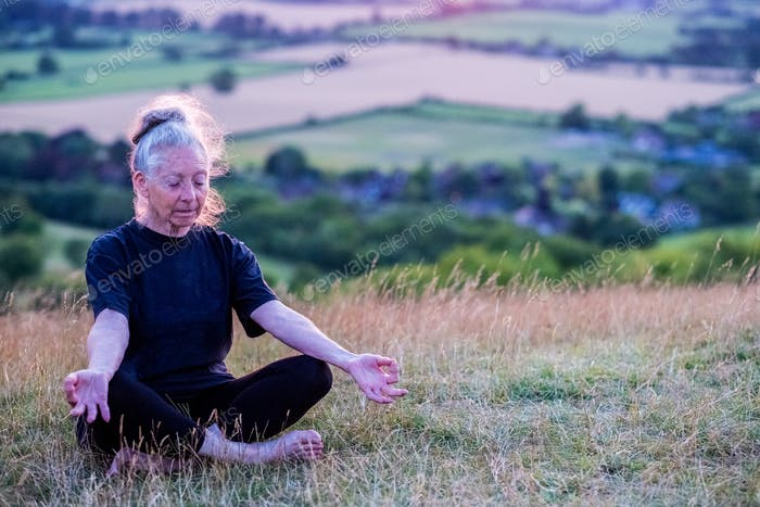 Senior woman taking part in a yoga class on a hillside.