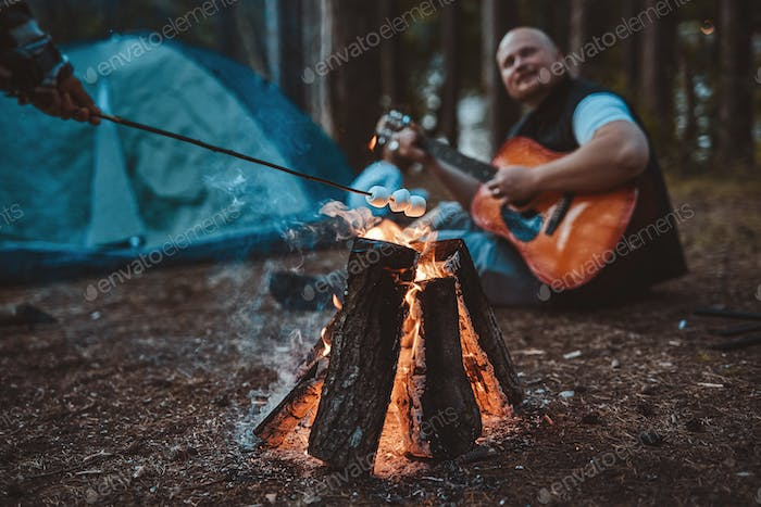 Marshmallow toasting on bonfire and bald man playing guitar