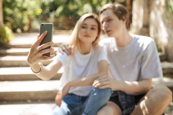 Portrait of young beautiful couple sitting and making selfie