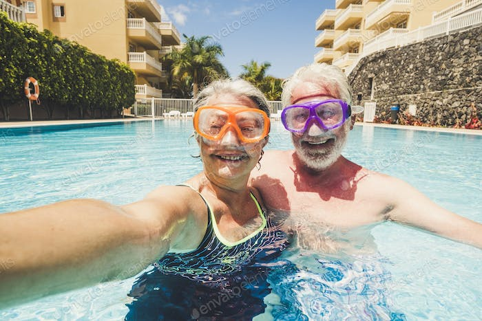 Funny couple of mature people enjoy summer and pool