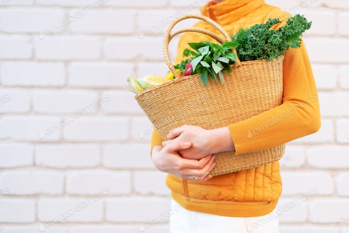 Woman hand holding straw basket with organic vegetables over brick background. Healthy food