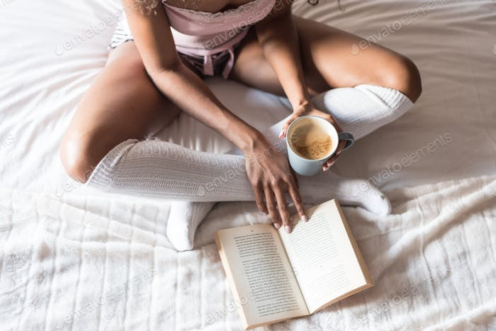 black woman reading a book and drinking coffee on bed with socks
