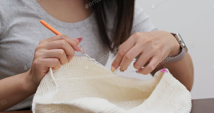Woman knitting with crochet hook and yarn at home