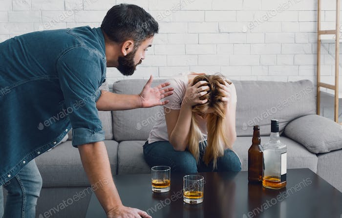 Drunken scandal. Woman holds her head and sitting on sofa, angry man swears with wife