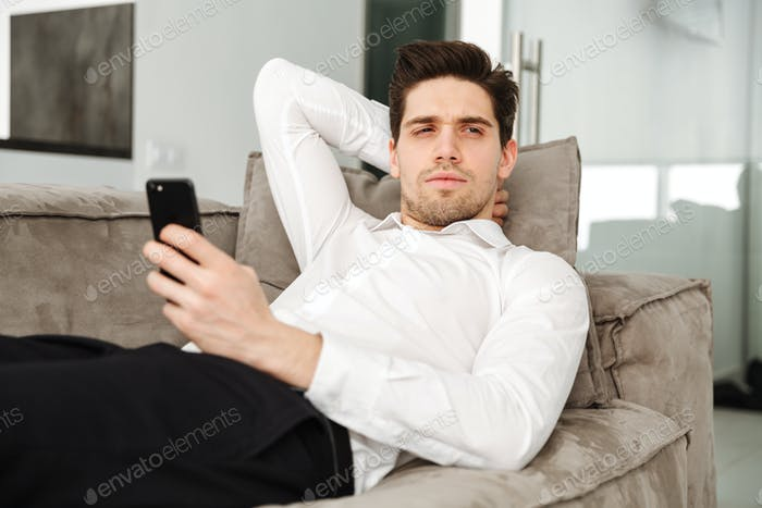 Concentrated young businessman in home lies on sofa