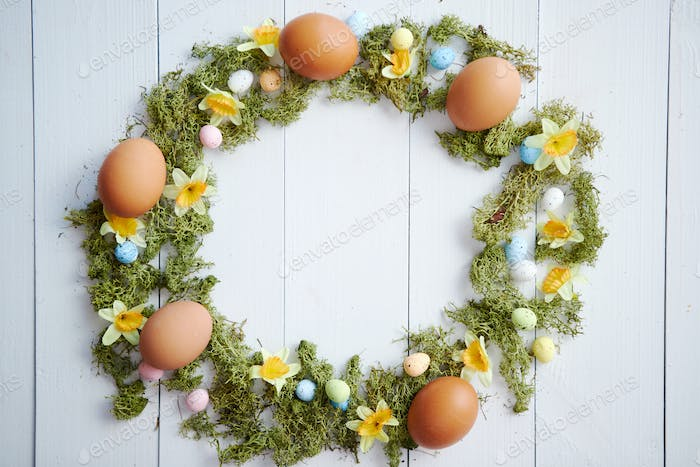 Colorful decorative Easter eggs wreath on white wooden table background