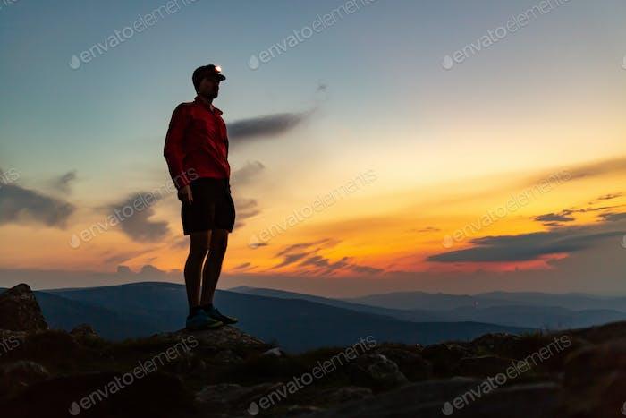 Trailrunner mit Stirnlampe auf dem Berggipfel in der Nacht.