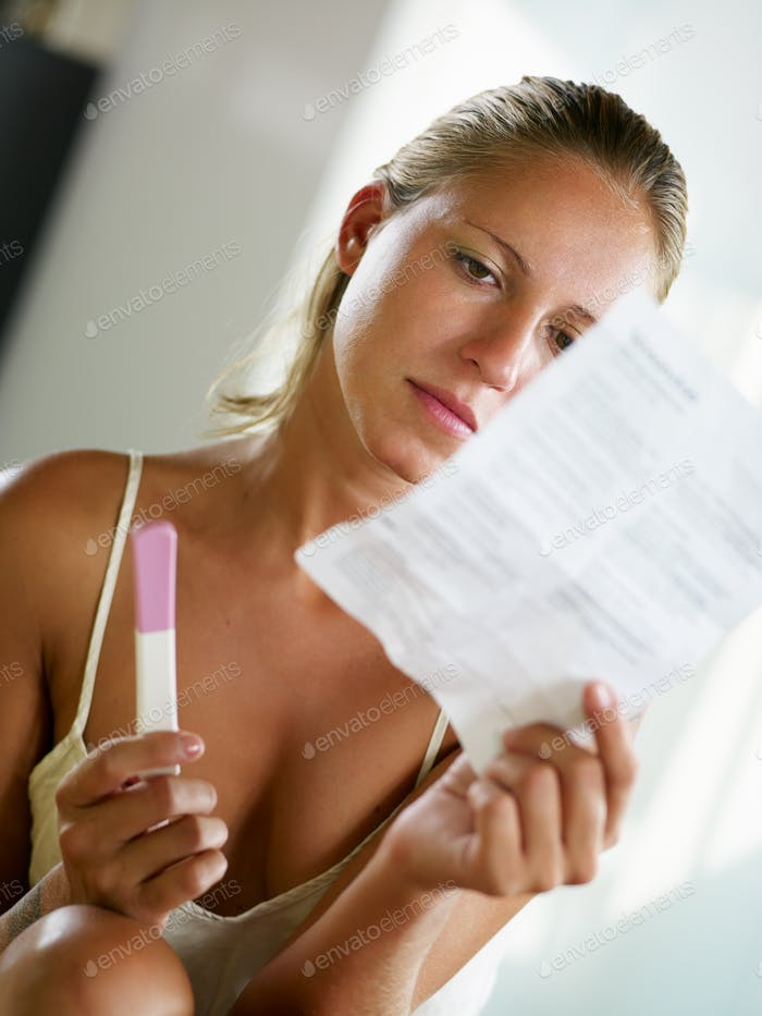 Young Woman Looking At Pregnancy Test Instructions