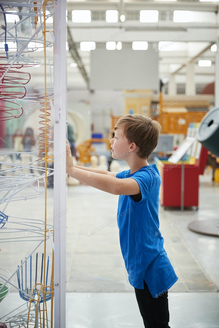 Boy standing looking at a science exhibit, vertical