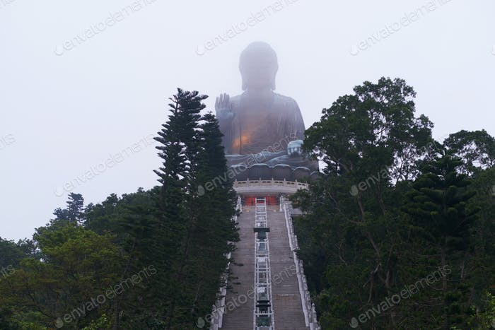 Giant Budha statue in fog on the vertex of mountain