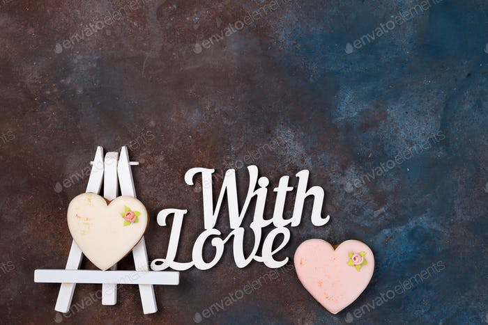 Cookies in the form of a heart in the icing on the easel as a picture on stone with copy space, flat