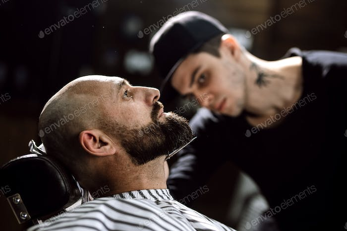 The barber dressed in a black clothes scissors beard of brutal man in the stylish barbershop