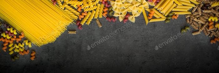 Verschiedene Arten von Pasta - Spaghetti, Penne, Fusilli, farbige Gemüse