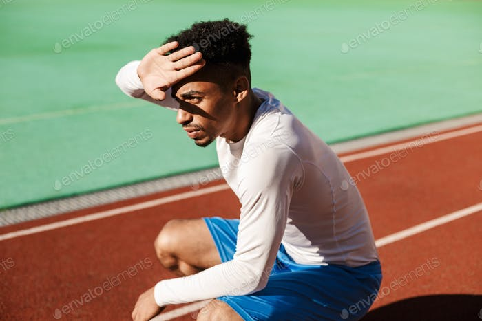 Thoughtful African American sportsman sit on one's haunches covering face from sun at city stadium