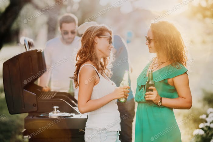 Portrait of happy girls enjoying light beers and having a good time at barbecue grill party