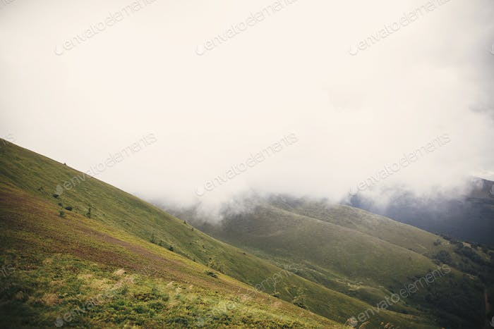 Landscape of foggy misty mountains under clouds