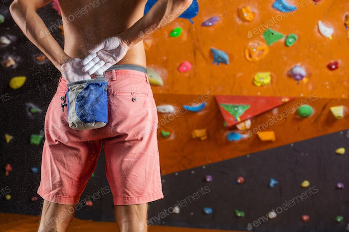 Rock climber putting chalk on hands to prepare for bouldering