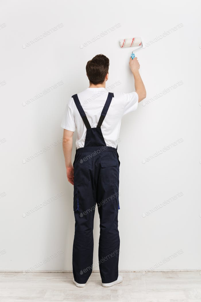 Full back view image of Young male builder painting wall