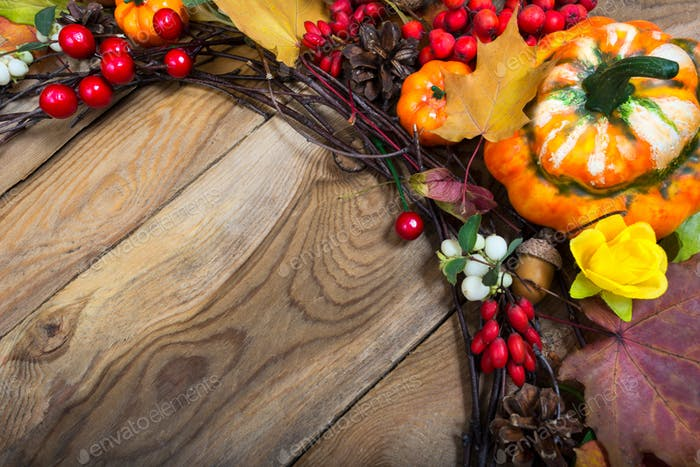 Fall background with decorative pumpkin, yellow rose and red ber