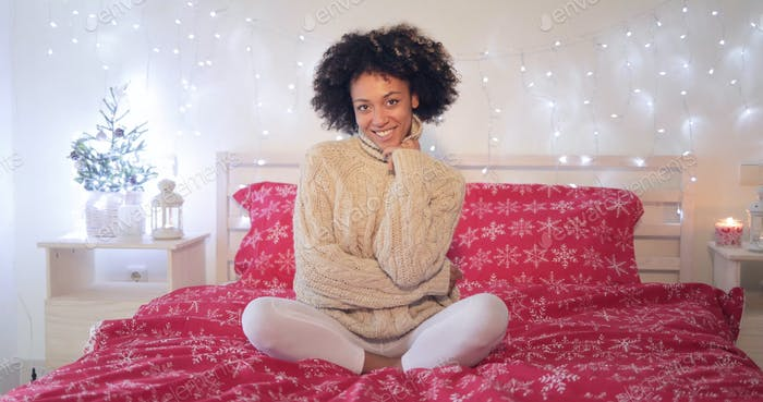 Smiling confident young woman sitting on her bed