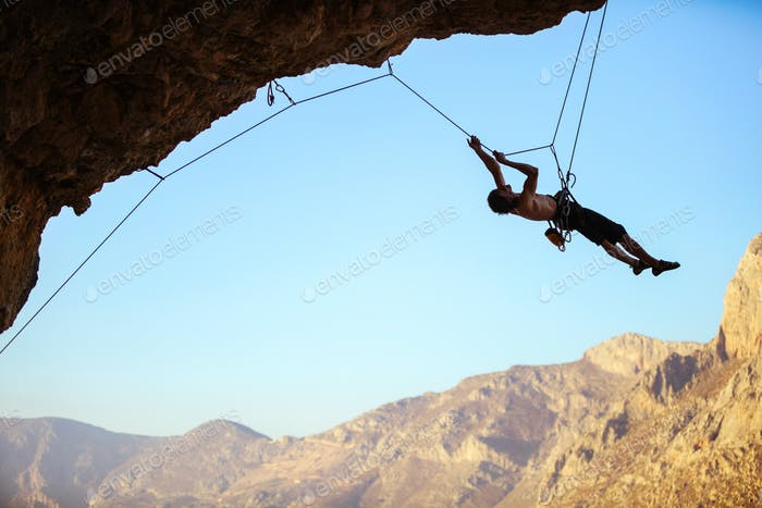 Rock climber pulling himself up using rope