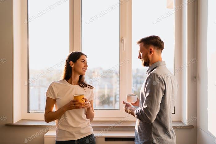 Mann und Frau trinken Tee in der Nähe des Fensters