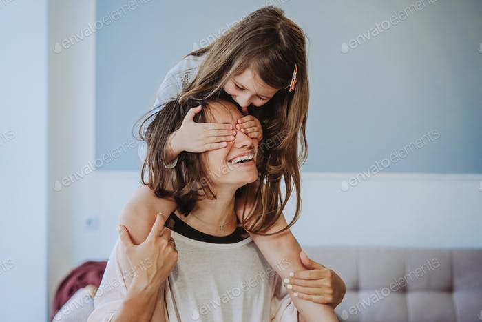 beautiful little daughter piggybacking on her happy mother
