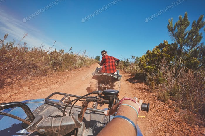 Young man driving ATV in nature