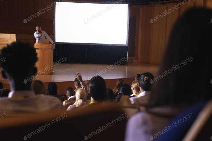 Businessman listening and asking in the auditorium