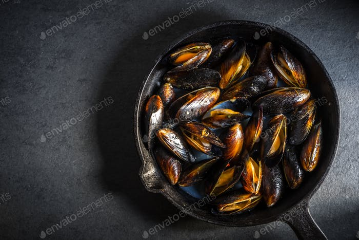Mussels on a cast-iron frying pan on a gray background free space