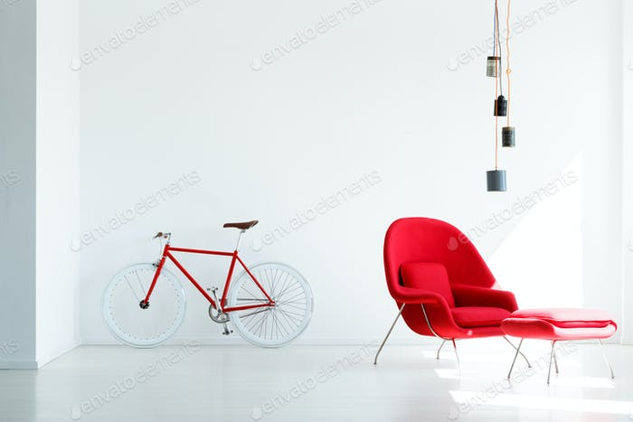 Red bicycle and armchair under lamp in white minimal apartment i