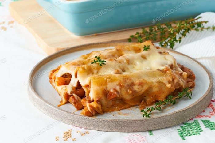 Cannelloni Pasta mit Füllung von Hackfleisch, Tomaten, gebacken mit Bechamel