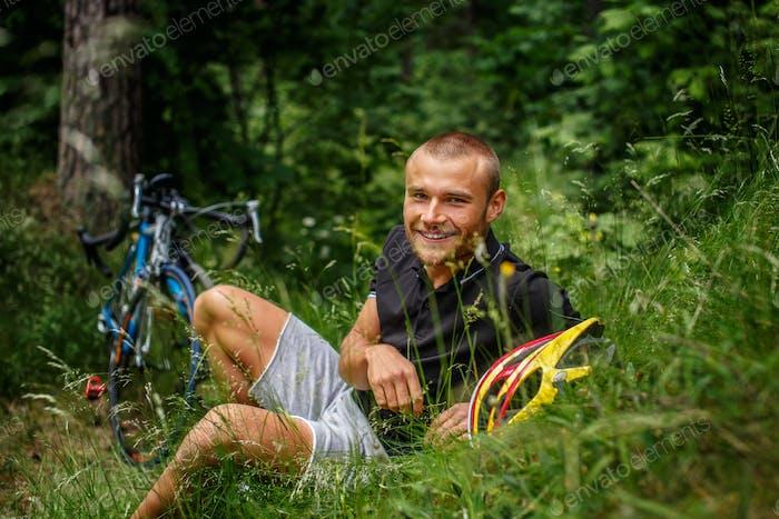 Mann liegt auf Gras im Wald.