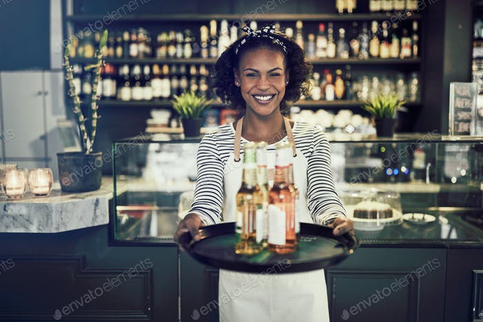 Smiling young African server carrying drinks in a restaurant