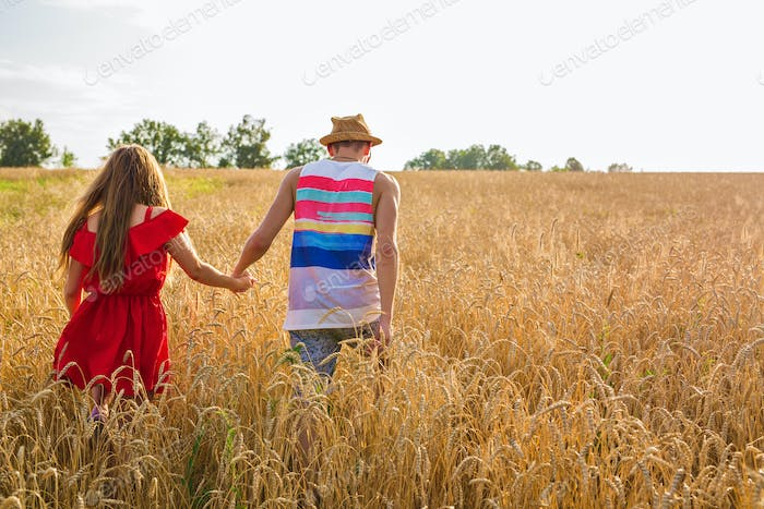 Young couple holding hands in the wheat field on sunny summer day