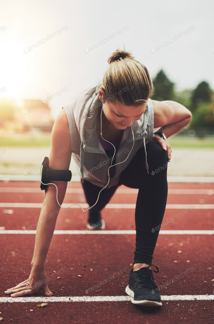 Athletic young blonde woman stretching on stadium