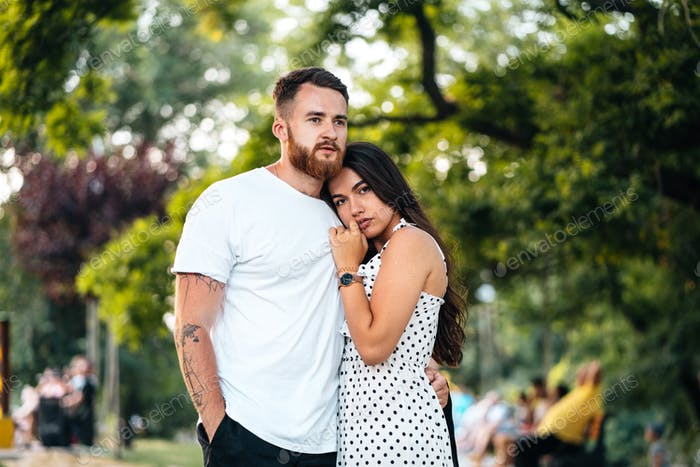 Handsome guy hugging his girlfriend in the park