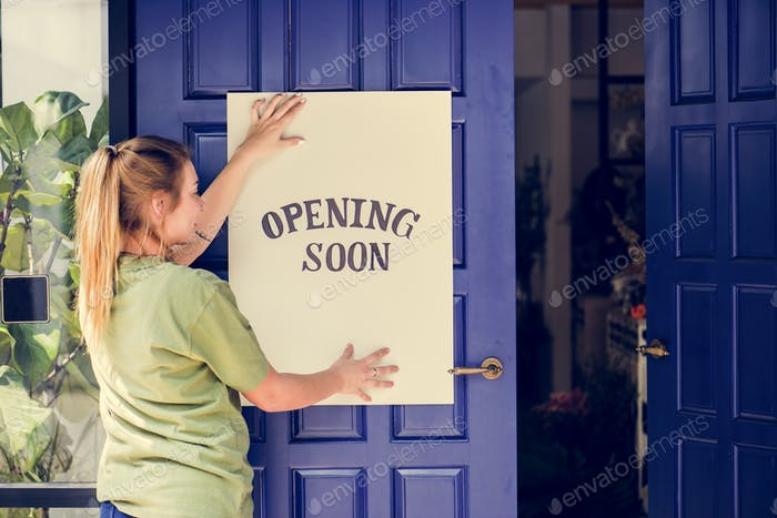 Woman putting on store opening soon sign