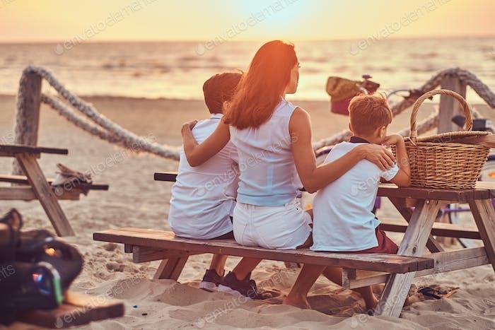 Mutter mit ihren Söhnen sitzen auf einer Bank und schaut auf den hellen Sonnenuntergang auf der Meeresuste.