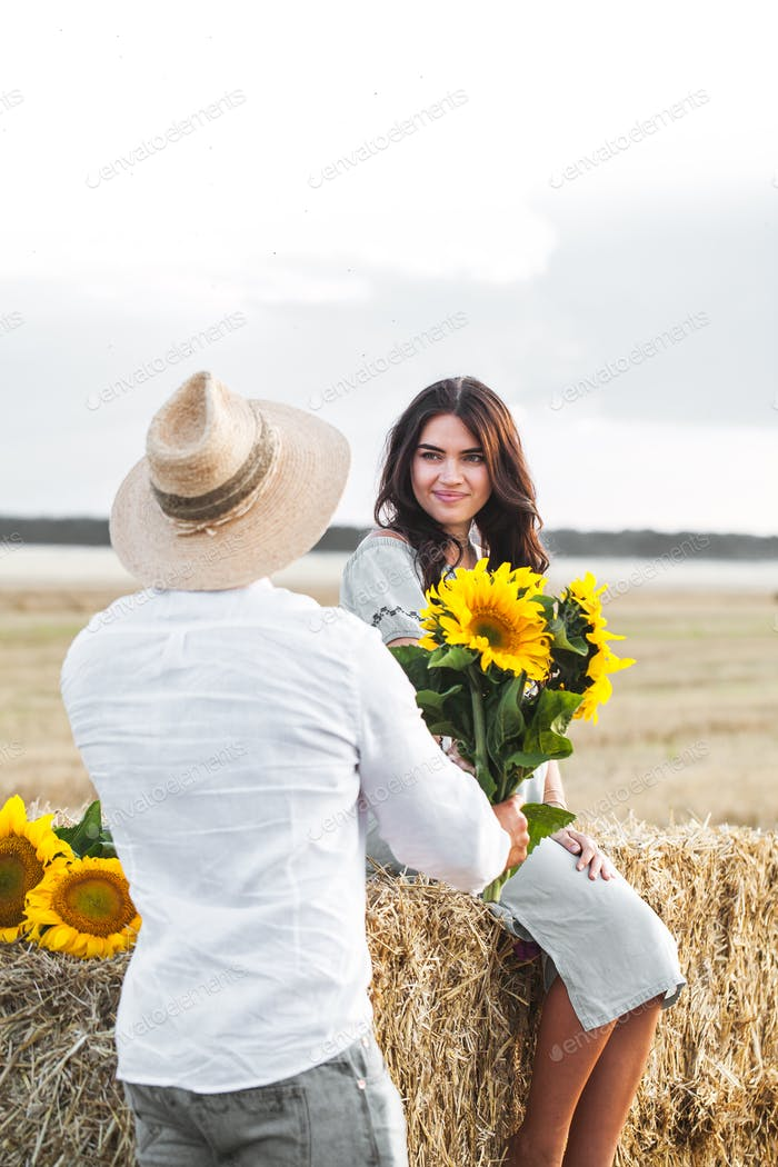 pregnant with her husband in the manger. Beautiful couple with sunflowers