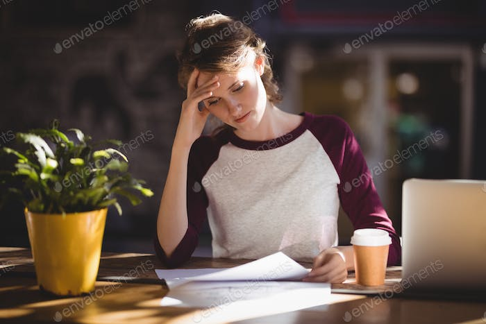 Troubled young female designer reading paper at coffee shop
