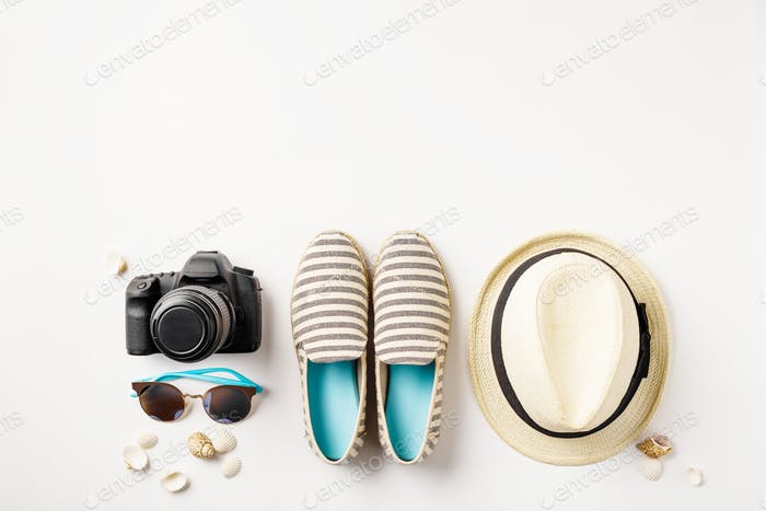 Flat lay traveler accessories on white background with palm leaf, camera and sunglasses