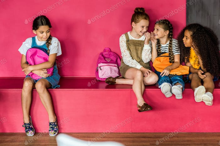 group of schoolgirls laughing and gossiping on their classmate at school