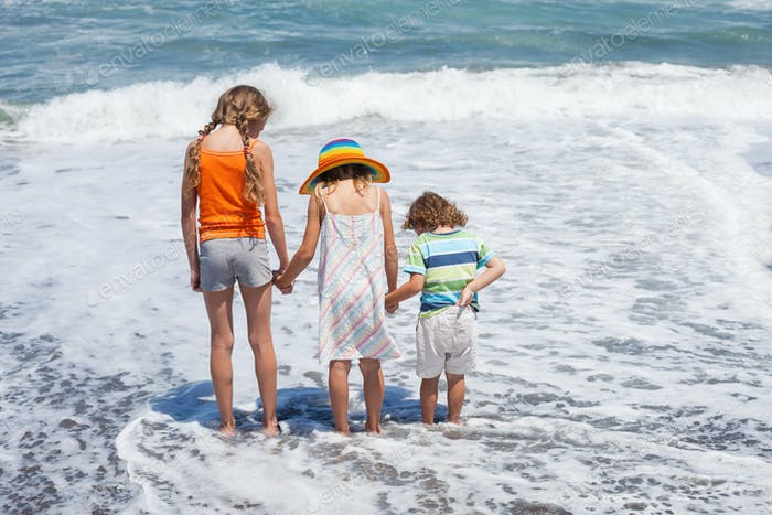 Three happy children playing on the beach at the day time