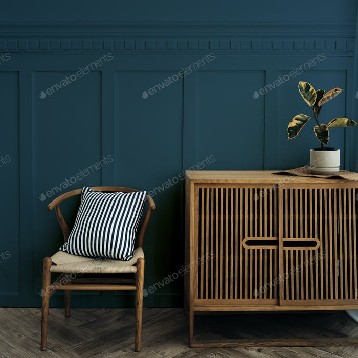 Scandinavian vintage wood cabinet with chair by a dark blue wall