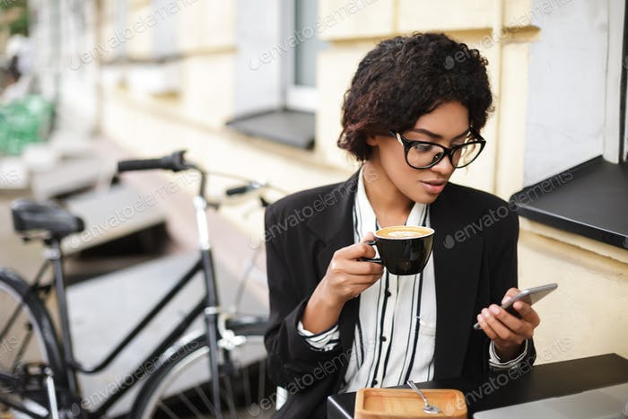 African American girl in glasses sitting at the table of cafe with cellphone and cup of coffee