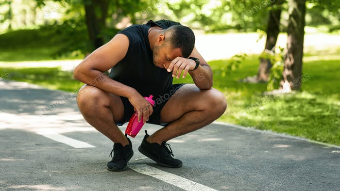 Exhausted black sportsman resting on jogging track after intensive workout, empty space