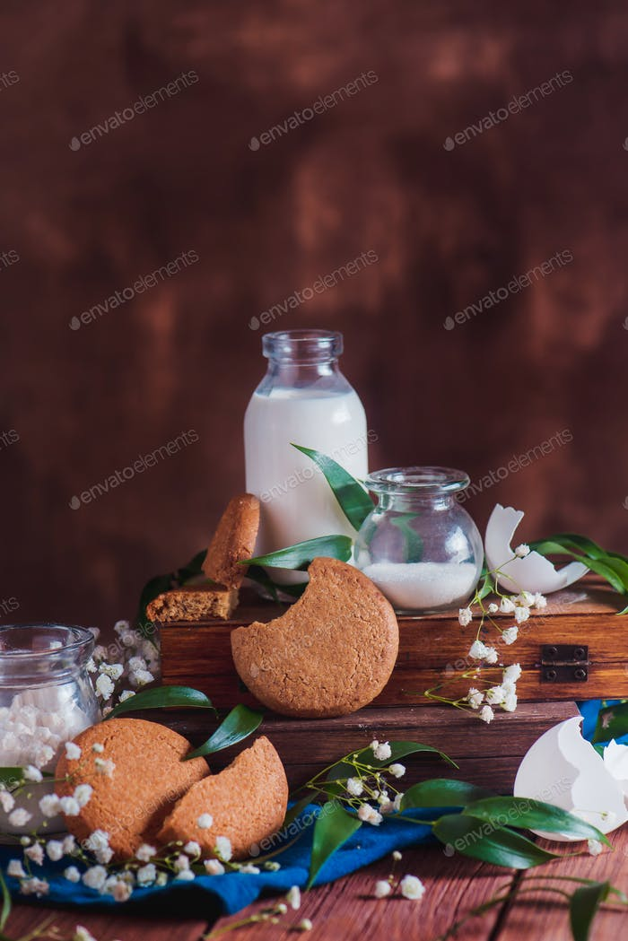 Homemade cookies with baking ingredients, a bottle of milk and an eggshell on a warm wooden
