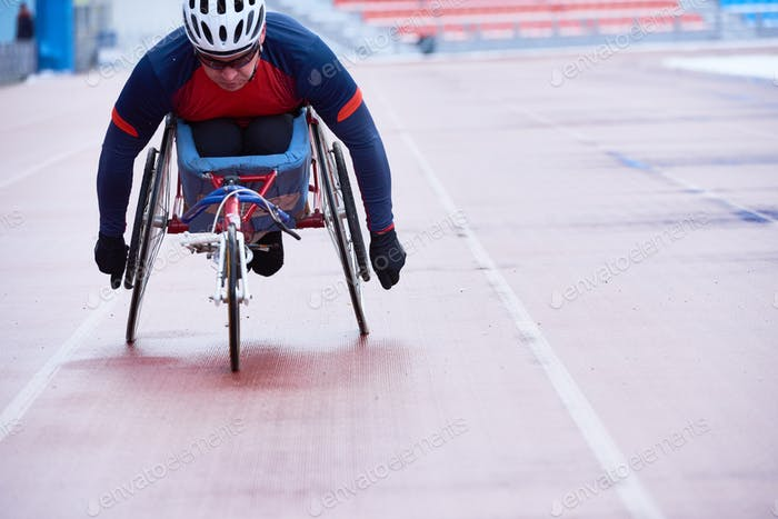 Determined athlete in sportswear and helmet participating in wheelchair race